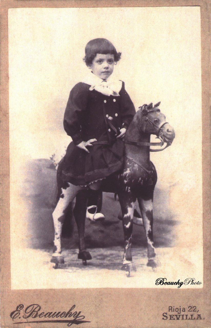 Niño vestido de negro en caballito de cartón