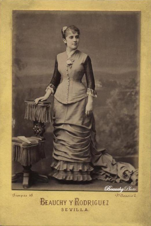 Mujer de cuerpo entero apoyada en una mesa